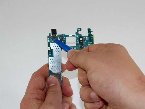 Image 2/2: Turn the motherboard around and use a plastic tool to undo the connection of the front camera.