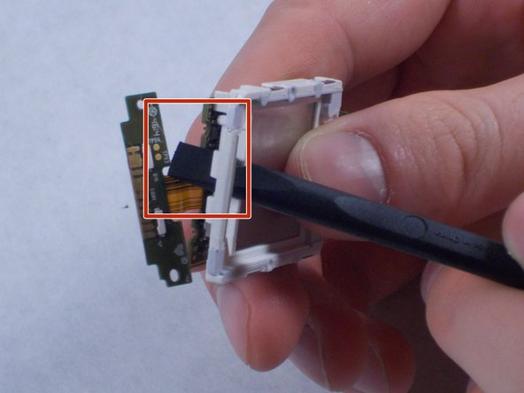 Use the spudger tool to poke out the exposed motherboard section as seen in  the photo.