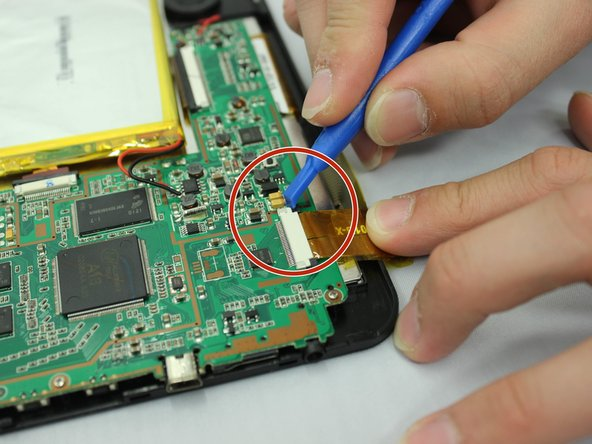 Image 2/3: Use your fingers to gently pull the medium width yellow ribbon cable out of the white connector.