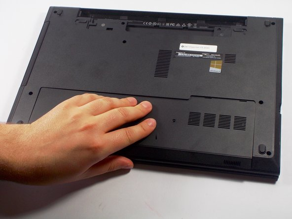 Image 3/3: Slide the bottom cover towards you and remove it from the laptop base. Put the cover aside.