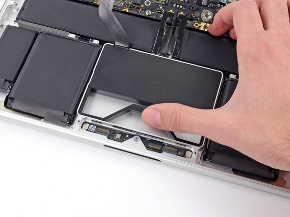 Image 1/3: While holding the spring bar depressed, tilt the SSD assembly up out of its cavity.