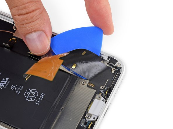 Carefully slide your pick from the corner of the battery to the corner of the iPhone to separate the  portion of the flex cable adhered to the outer frame.