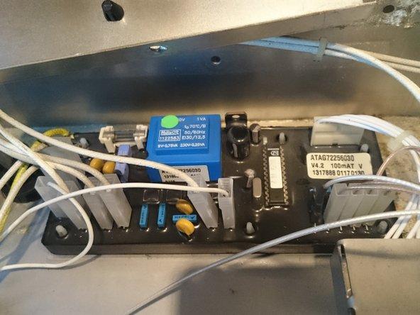 De zekering en electronica bevinden zich onder een afdekplaat links-achter. Die hangt vast met een vijs langs de achterkant  het fornuis.