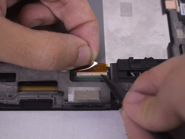 Using the sharp end of the plastic spudger, lift the ZIF lock to release the ribbon and pull rearwards to separate.