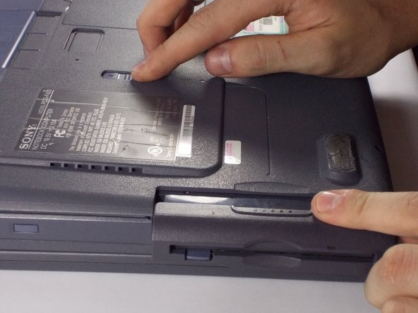 Slide tab in the direction of the arrow and pull out the floppy drive.