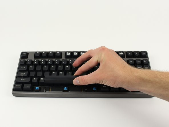 Pull the large keycap upward with your fingers until the cap separates from the plastic rings underneath the cap. If the metal bar beneath the cap comes loose during removal, snap it back in place.