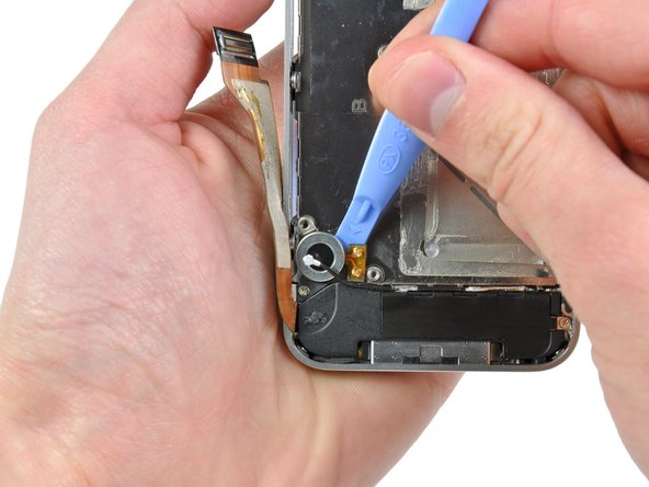 Use the edge of a plastic opening tool to pry the vibrator off the adhesive securing it to the frame of the iPhone.