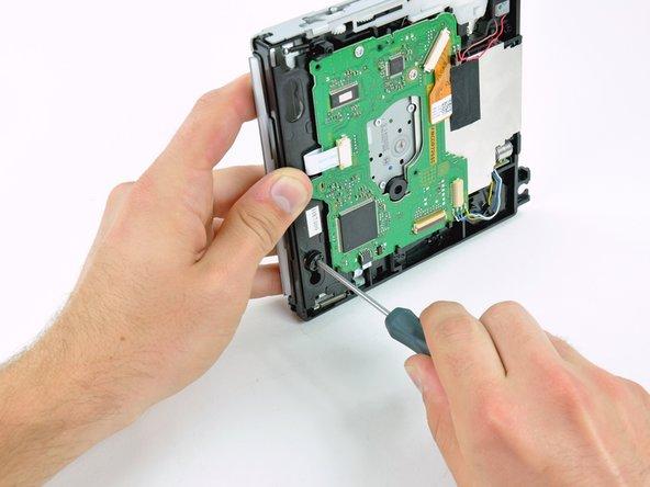 前と同じ手順で、内蔵DVDドライブの正面側に沿って装着された2番目のゴム製はと目金を取り出します。