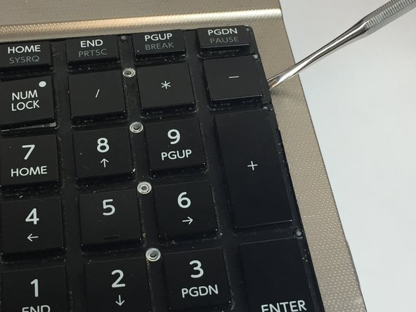 Use a plastic opening tool to pry up the keyboard.