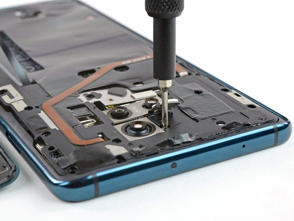 A flock of screws hold the NFC coil, antenna, and graphite heat conductor pad in place. One hides behind a tamper-proof sticker, and another one lurks under the camera flash module—a strange place for a screw.