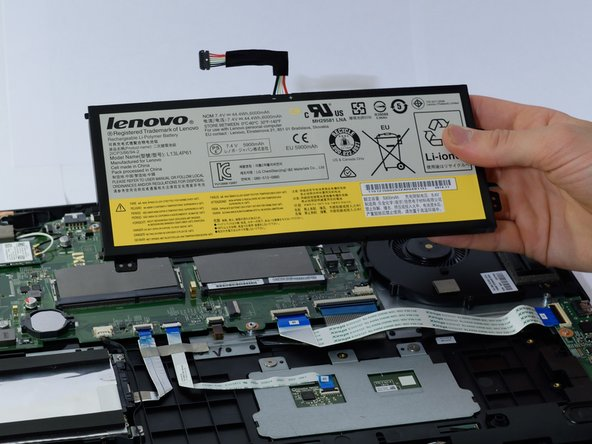 Gently lift all four corners of the battery to remove it from the laptop.