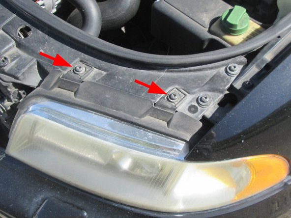 Image 2/2: There are two other screws next to the headlight assembly, but not attached to it. These are unrelated and should be left alone.
