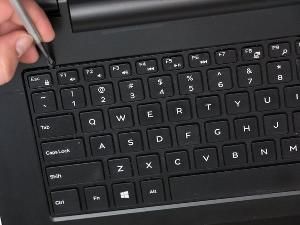 Using a metal spudger, gently pry the keyboard tabs inwards until they loosened. You should hear a click.