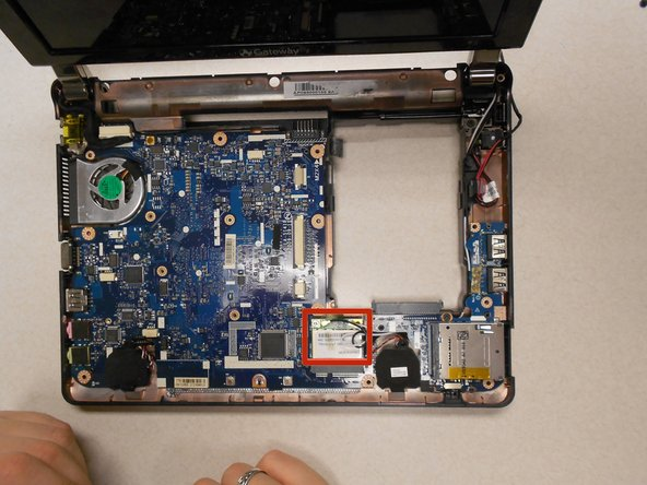 Image 1/2: Remove the one (1) 5mm screw holding the card to the motherboard using a Phillips #0 screwdriver.