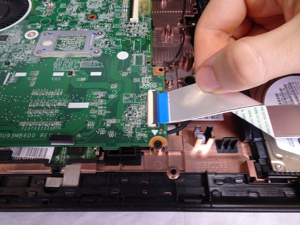 Remove the USB/AUX port ribbon cable from the ZIF connector on the motherboard.