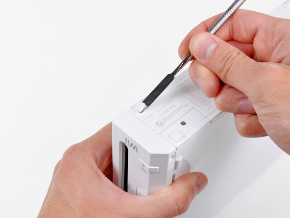 Use a metal spudger to remove the rubber foot stuck to the side of the Wii near the DVD drive opening.