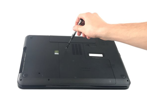 "Loosen the 7.25mm screw on the bottom of the laptop holding the ""L"" shaped cover down."