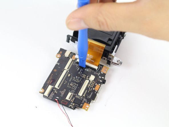 Use the plastic opening tool to remove the orange ribbon on the motherboard by wedging the tool under the ribbons black tab, and carefully prying upwards.