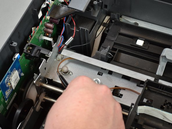 Unwrap the carriage belt from the hook on the other side of the printer using the tweezers by pulling to the left and up.