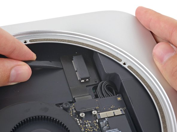 Slip the flat end of a spudger under the SSD cable to lift it off the adhesive holding it to the Mac Mini.