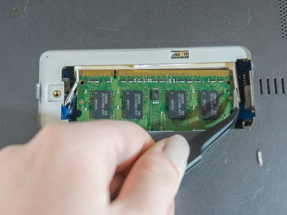 Using the tweezers, push the edges of the metal clasps holding the ram card away from the card. You should see the card pop upwards.