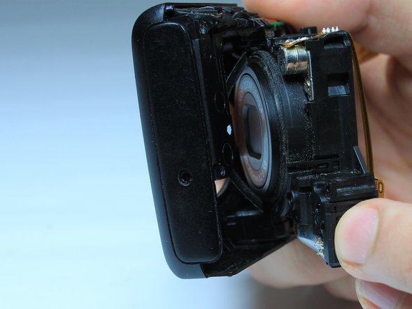 Image 2/2: A thin circular ribbon should fall out from the front of the lens. Note its original location on the front cover for reassembly.