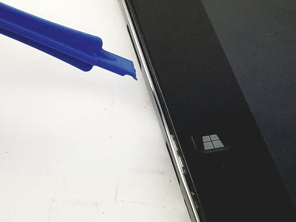 Slide one of the plastic opening tools in the crack on the side of the device with the windows button.