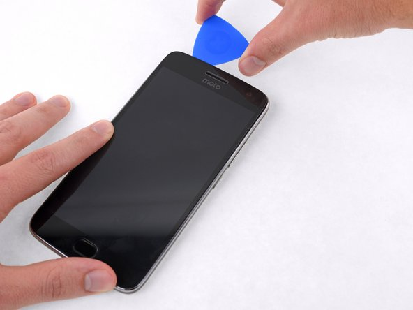 Continue cutting through the adhesive on the top and right sides of the phone.