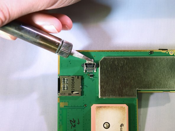 Gently and delicately heat up the solder holding the USB port to the circuit board.