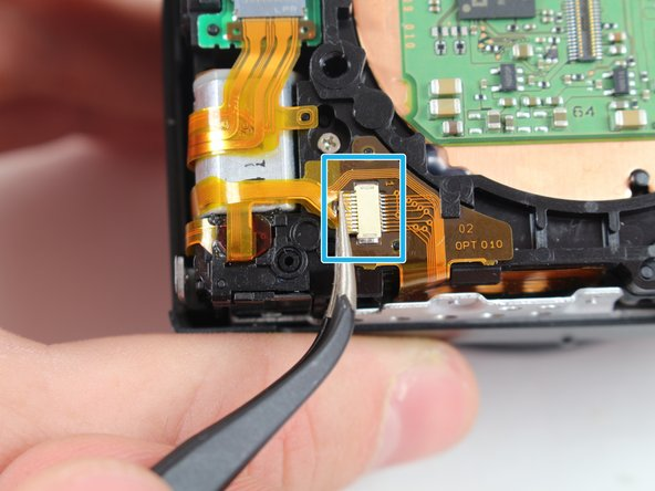 Image 2/3: Remove the bottom ribbon cable with the fine tip metal tweezers by pulling it toward the flash switch side of the camera.