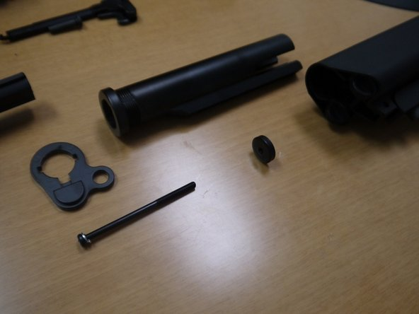 Image 3/3: Optional: remove the screw securing the buffer tube to the gun, then remove the buffer tube/stock assembly. A round nut should fall out of the buffer tube after the assembly is removed (shown in third picture).