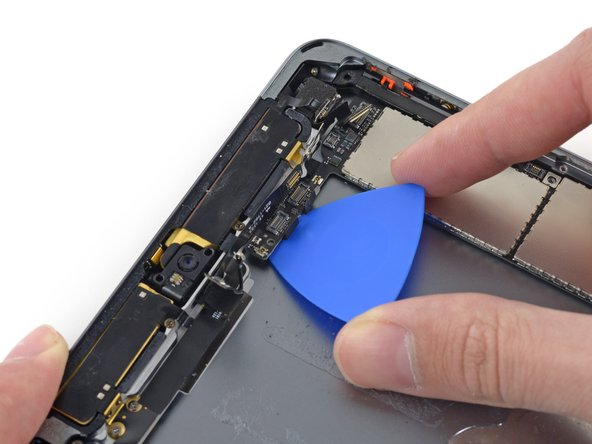 Image 2/3: Try to keep the opening pick as flat as possible to avoid bending or breaking the thin tab of the logic board.