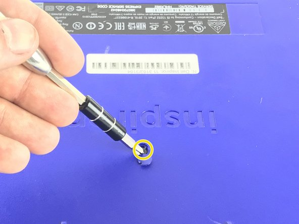 Use your screw driver to pry off the plastic cover exposing the last screw in the middle.