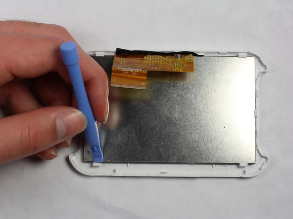 Use the spudger to pry the LCD from the clamps holding it to the case.