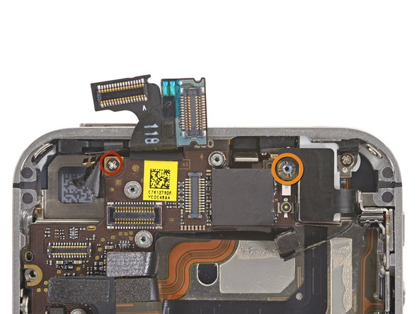 Image 1/1: Use a small flathead screwdriver to remove the 4.8 mm standoff screw near the headphone jack.