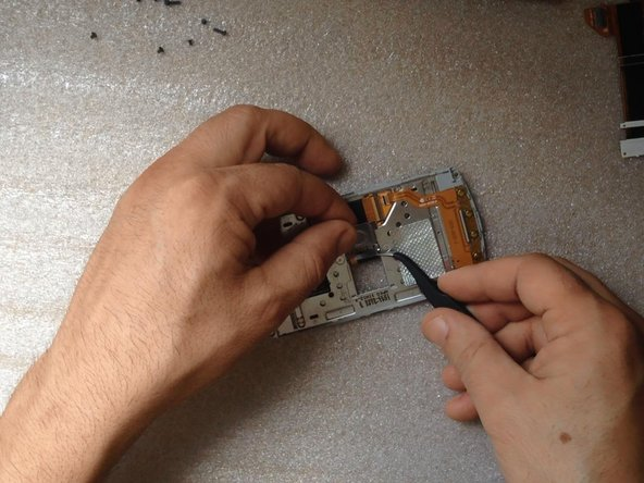 Now remove the small metal plate taped to the flex cable.