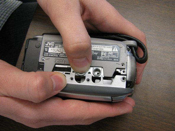Start from bottom of camera. Press and hold eject button with one hand.