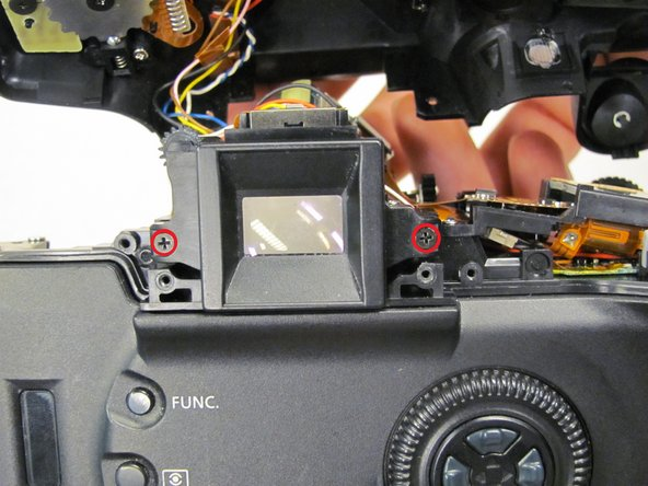 Remove the two 9.5 mm black screws that attach the inner eyepiece to the camera's body and remove the eyepiece.