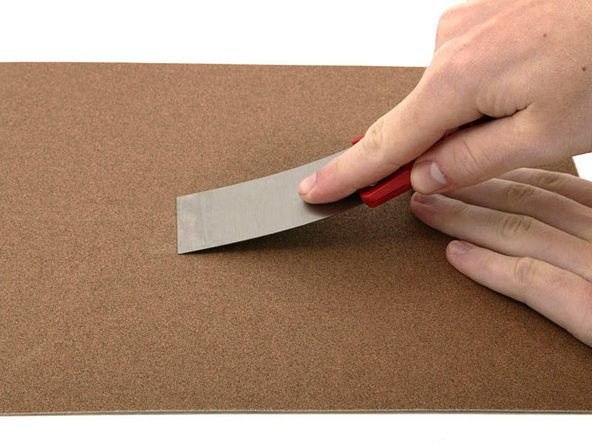 Image 1/1: You'll need a putty knife in order to open the case. A 1.5 inch thin putty knife will work well, but you'll want to grind the edge down. Rub the putty knife's short edge back and forth on a sheet of all purpose rough grit sandpaper (100 grit will work fine) until it attains a beveled edge.