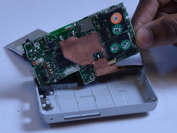 Using two fingers to grip the edge of the board, slide the motherboard out of the case to the right.