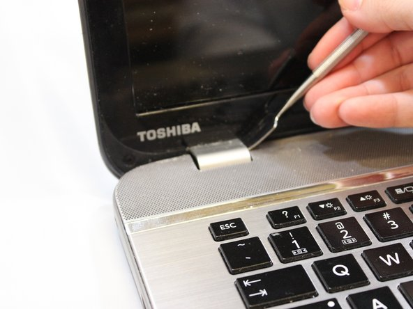 Using a metal spudger, insert the spudger around the edges and the bottom to detach the frame from the screen.