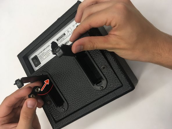 Locate the two battery terminals. As you begin to slowly remove the amplifier's back panel, feed the two battery terminals back to the amplifier so that they are no longer inside the battery cartridges.