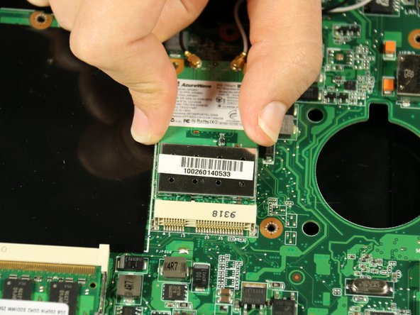 Use your hand to carefully lift up and remove the wireless network card from its connection to the motherboard.