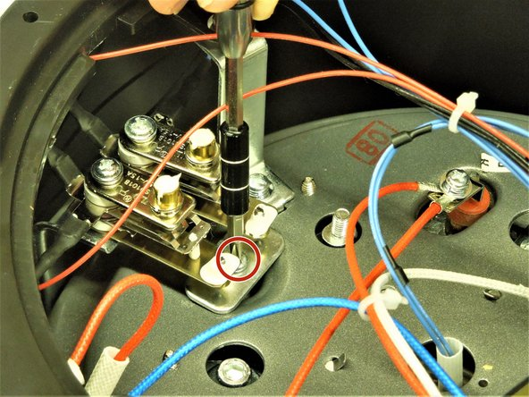 Remove the 10mm screw and metal plate beneath the electrical nodes using a Phillips #2 screwdriver.