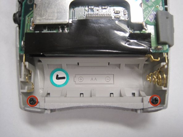 Using a Phillips #00 Screwdriver, remove the two 5.5mm screws from the sides of the battery compartment.