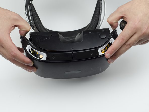 Using your fingers, carefully pry the black front panel free from the headset.