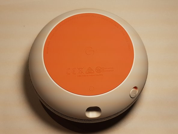 Der Google Home Mini wird von der Unterseite geöffnet. Hierbei handelt es sich um eine gummierte Kunstoffscheibe die mit dem Gerät verklebt ist.