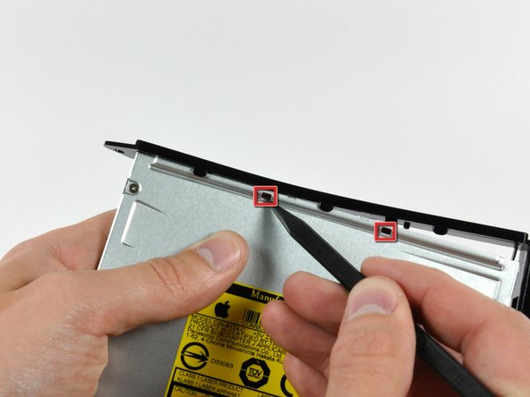 Push the optical drive bracket tabs out of their slots in the top of the optical drive.