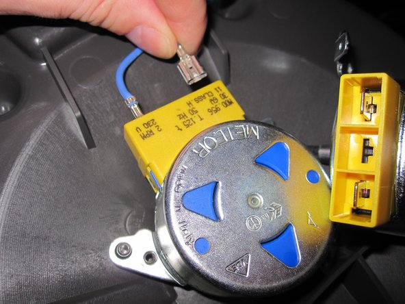 Nun siehst du den Motor offen vor dir. Es gibt zwei weitere Sicherheitsschrauben, solche wie du eben grade außen abgeschraubt hast. Wenn du den Motor tauschen willst musst du die beiden Kabel vom alten Motor abziehen und am neuen befestigen. Er kann dann wieder an die Stelle des alten Motors geschraubt werden.
