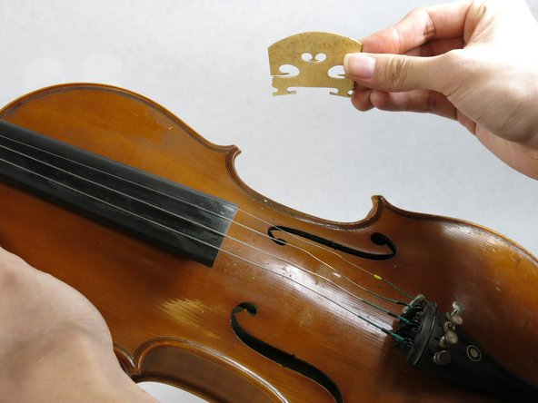 Remove the bridge gently from the violin.